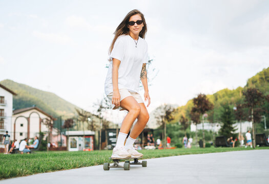 Slim young woman with long blonde hair in light sports clothes on longboard in outdoor skatepark at sunset