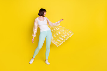 Full length photo of charming happy nice young woman shawl fly wind summer isolated on yellow color background Wall mural