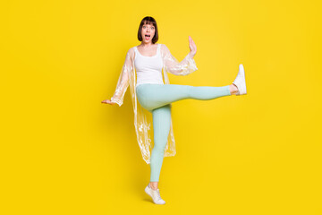 Full length photo of amazed young positive woman raise leg dance wear casual clothes isolated on yellow color background Wall mural