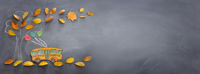 Back to school concept. Top view banner of school bus next to tree sketch with autumn dry leaves over classroom blackboard background