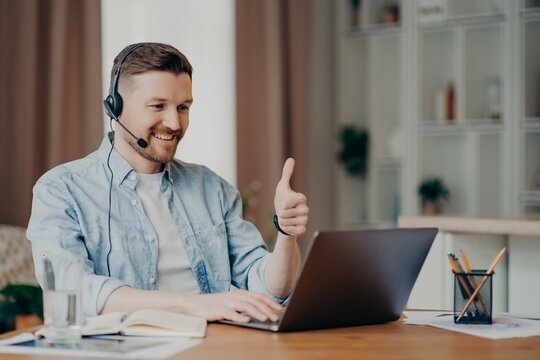 I like it. Glad bearded adult man has video conference keeps thumb up likes something focused at laptop computer has distance job interview dressed casually. Professional call center agent working