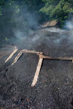 Traditional Charcoal making in Gozd Martuljek. Slovenia. Smoking mound of wood.
