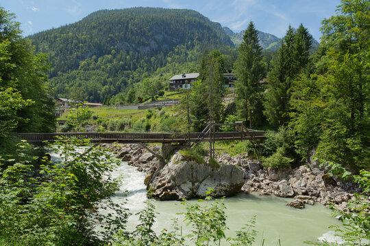 Blick auf Holzbrücke über einen Fluss.