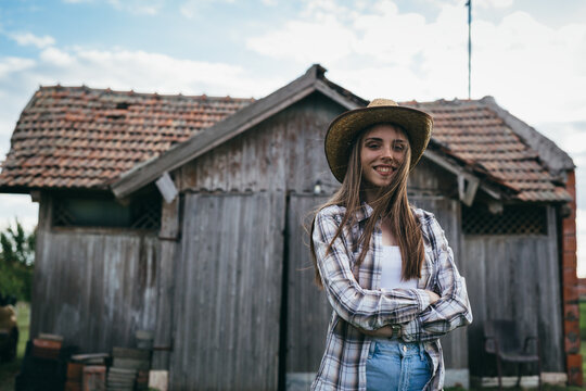 woman rancher standing in front of barn