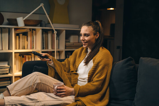 woman relaxing at home watching television. evening scene