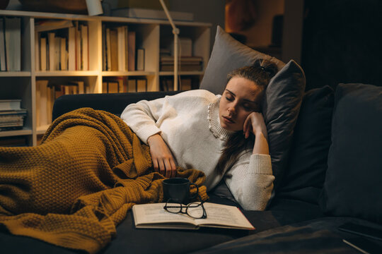 woman fell asleep while she was reading book at home