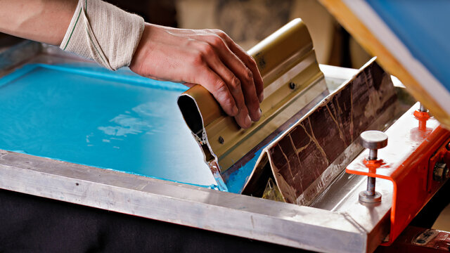 selective focus photo of male hand with a squeegee. serigraphy production. printing images on clothes by silk screen method in a design studio