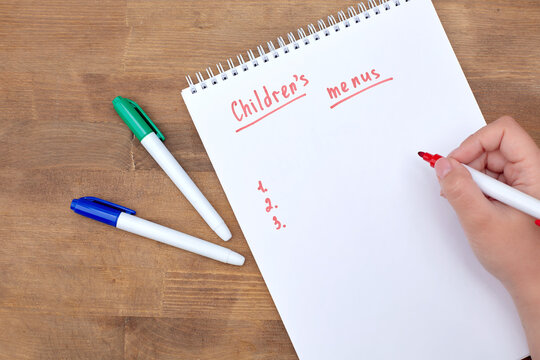 A to-do list in a spiral notebook on a wooden table. An empty space for the text. In the girl's hand is a red marker and an inscription, a children's menu