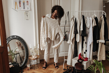 Fototapeta Stylish young dark-skinned curly lady in beige pants and jacket smiles, poses in dressing room an holds hanger with trendy knitted sweater. obraz