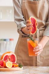 Fototapeta Woman squeezing grapefruit into glass in kitchen obraz