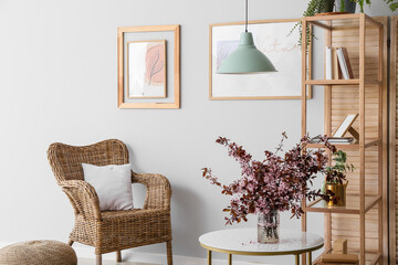 Fototapeta Vase with blossoming branches on table in interior of living room obraz