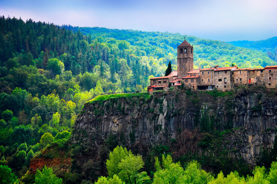 Castellfollit de la Roca, Garrotxa, Province of Girona, Catalonia, Spain, Europe. Beautiful view, ancient church and town houses at the top of huge basalt cliff and mountain covered with green wood