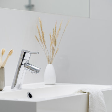 Close-up on silver tap in bathroom washbasin