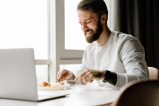 Bearded european man working with laptop while having breakfast