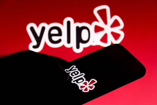 July 14, 2021, Brazil. In this photo illustration Yelp logo is seen on a smartphone and a pc screen.