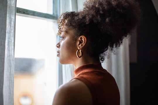 African american female looking out of window in home