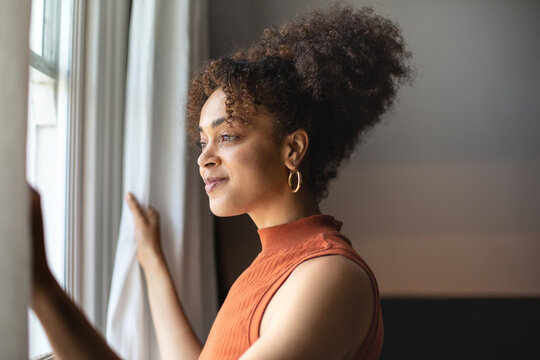 Happy African American female looking out of window in home