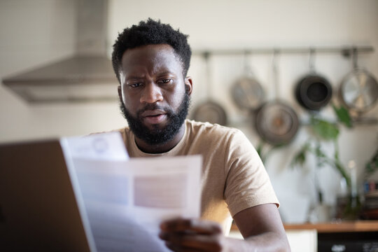African American male looking at bills and paperwork