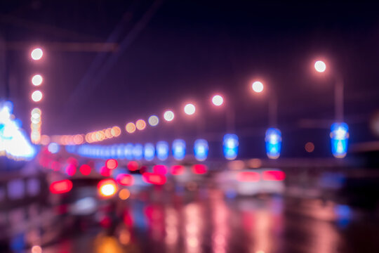 Blurry lights of moving cars and lanterns reflecting on the wet asphalt in the night city.