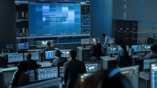 Group of People in Mission Control Center Trying to Establish Video Connection on a Big Screen with an Astronaut on Board of a Space Station. Flight Control Scientists Sit in Front Computer Displays.