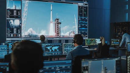 Fototapeta Group of People in Mission Control Center Witness Successful Space Rocket Launch. Flight Control Employees Sit in Front Computer Displays and Monitor the Crewed Mission. Team Stand Up and Clap Hands. obraz