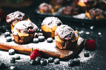 Muffin. Chocolate muffins with stawberry. Muffins on wooden stand with powder sugar.