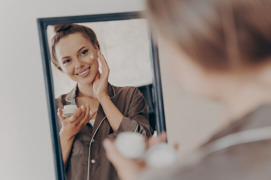 Reflection in mirror of beautiful woman in silk pajama smiling while applying face cream for deeper repair
