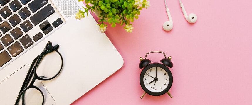 Top view of a small green tree, spectacle, black alarm clock and glasses, white wired headphones and laptop on a pink background. Business conceptual.