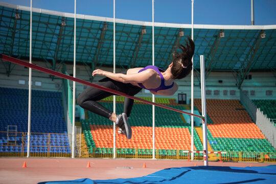 Sportswoman doing high jump exercise