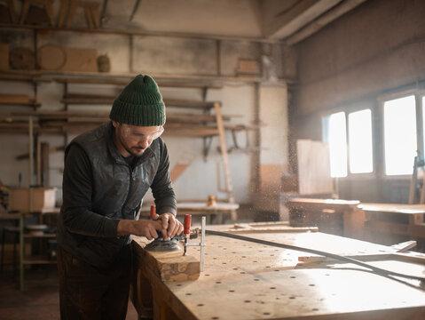 Male carpenter polishing wooden plank