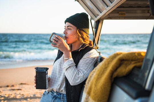 Young woman enjoying drink in mug while beach car camping alone