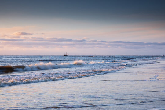 fishing boat on stormy sea at sunset