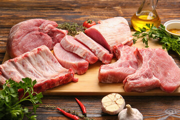 Board with slices of raw pork meat, parsley and garlic on wooden background