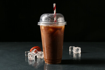 Plastic cup with coffee and ice on dark background