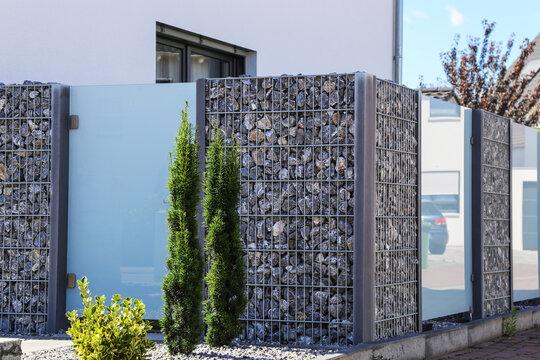 Nahaufnahme einer Gabione als moderner und hochwertiger Sichtschutz und Grundstücksbegrenzung an einem Wohnhaus