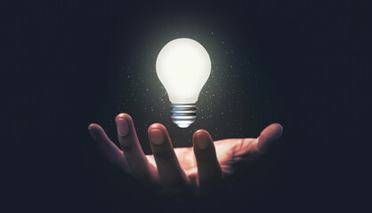 Fototapeta Hand hold glowing idea light bulb and innovation thinking creative concept on success inspiration dark background with solution creative business design. obraz