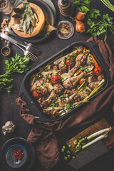 Tasty roasted chicken drumsticks with vegetables in cast iron casserole on kitchen table background...
