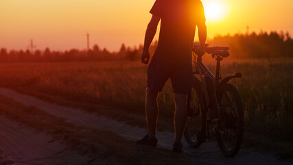Fototapeta The silhouette of a cyclist at sunset in a field. Cycling on a summer evening copy space obraz