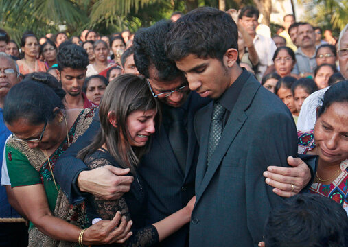 Jacintha Saldanha's widower Barboza and her children Lisha and Junal mourn during her funeral at a cemetery in Shirva