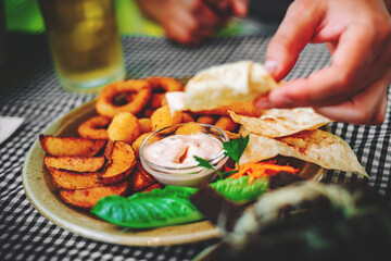 man hand and plate with snacks on table background on bar or pub