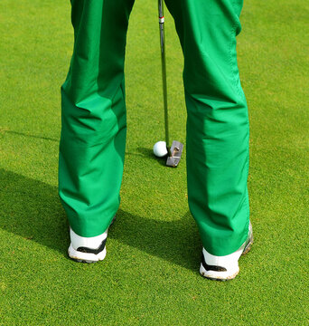 Golf player in green pants and white sneakers hitting the ball with an iron stick on a golf course in Costa del Sol Andalusia, southern Spain