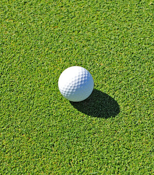 Close-up of a white golf ball on a green grass background. Golf concept on a golf course. Playing golf ball in green.