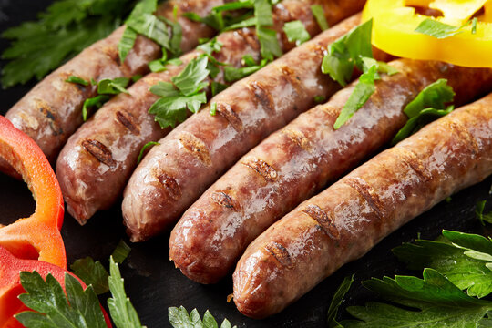 Grilling sausages on barbecue grill with greens