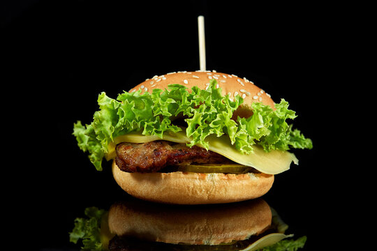 Burger with meat and cheese on black background.