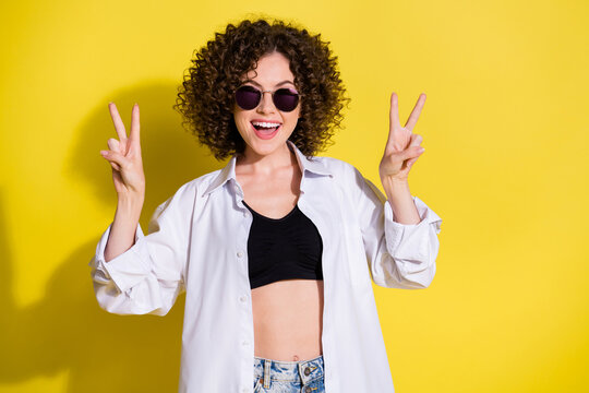 Photo of young happy cheerful positive lovely pretty funky girl showing v-sign isolated on yellow color background