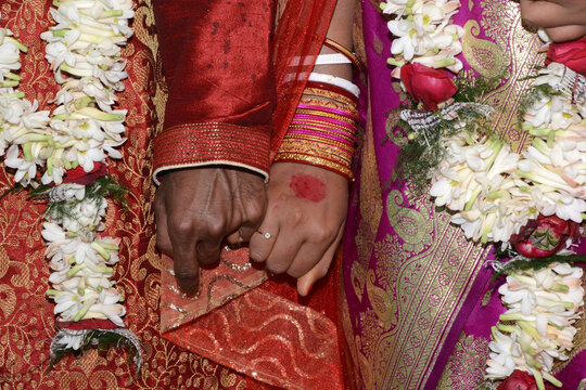 Closeup shot of an Indian couple holding hands during a traditional weddin