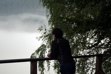 Fototapeta Postać sylwetka kobiety opartej o balustradę na tarasie widokowym obraz