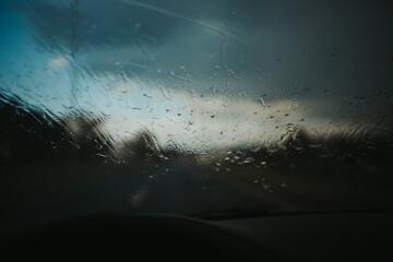 Fototapeta Blurred shot of the road seen through a car window covered by raindrops obraz