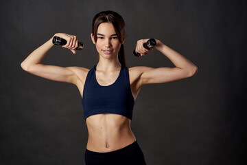 Obraz athletic woman slim figure dumbbells in the hands of fitness pumped up muscles - fototapety do salonu