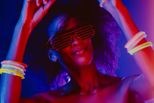 Fashionable woman with afro hairstyle dancing in room with colorful lamps. Cyberpunk style or hipster with fluorescent bracelets and glasses. Night club, futuristic outfit. Sexy lady concept.